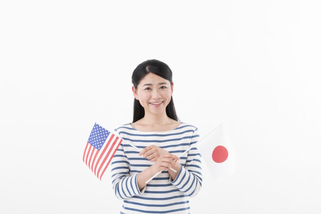 アメリカと日本の国旗を持つ女性